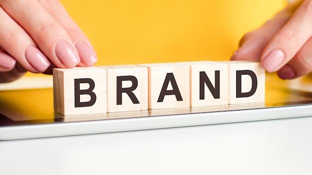 Le mani delle donne mettono un blocco di legno con il marchio delle lettere sulla superficie del blocco note. può essere utilizzato per il concetto di business. sfondo giallo
