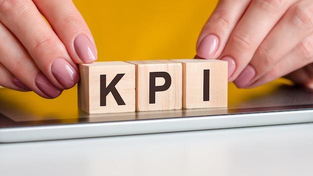 Le mani delle donne mettono un blocco di legno con le lettere kpi sulla superficie nera del blocco note. può essere utilizzato per affari, marketing, istruzione, concetto