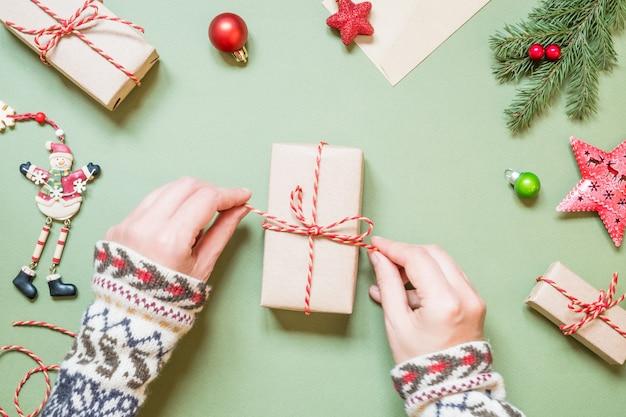 Le mani delle donne legano un arco su un regalo di natale