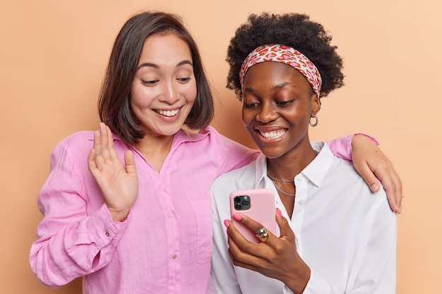 Le donne si divertono a fare videoconferenza tramite smartphone onda ciao ad un amico comunicare a distanza abbracciare e vestirsi casualmente sul muro marrone usare le moderne tecnologie