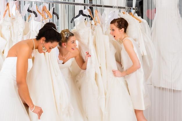 Donne che si divertono durante il montaggio dell'abito da sposa nel negozio di moda per matrimoni