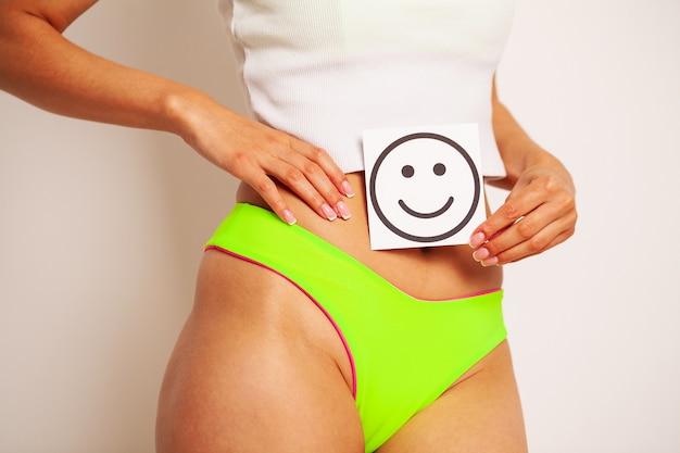 Salute delle donne, bel corpo femminile in mutandine con carta di sorriso.
