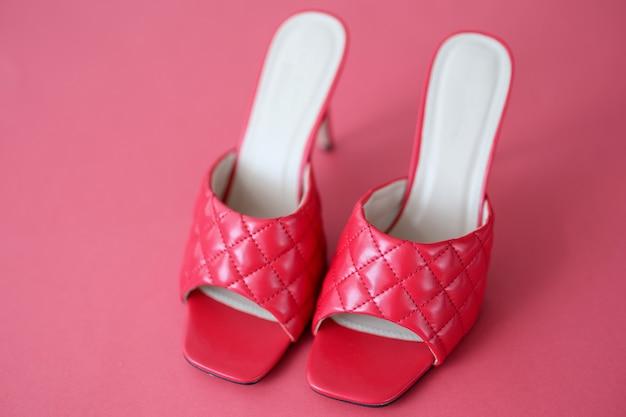 Scarpe da donna con tacco alto in piedi su sfondo rosso