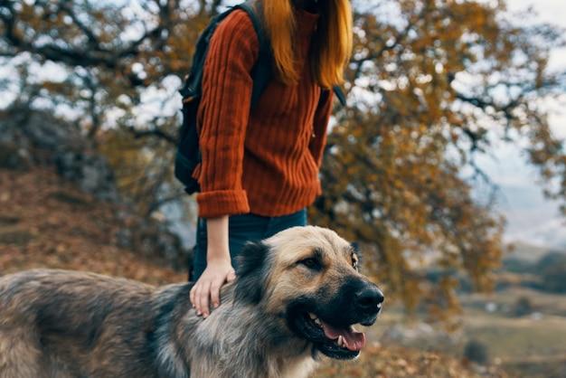 Escursionista di donne facendo una passeggiata con il cane in natura