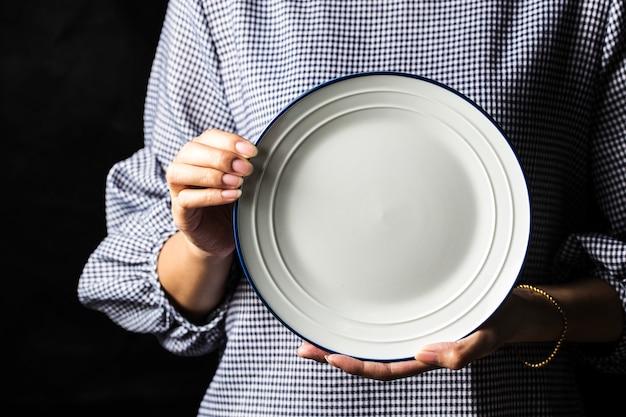 Le donne tengono i piatti bianchi nelle loro mani.