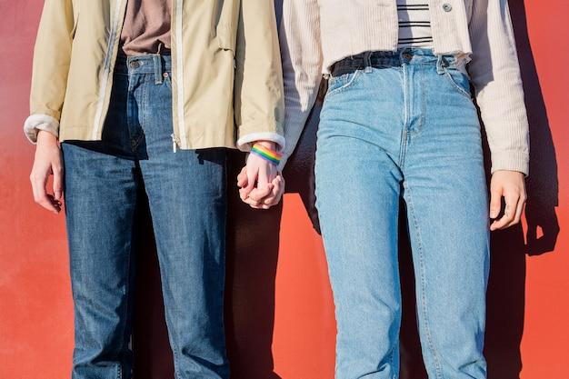 Donne che si tengono per mano con il simbolo dei diritti omosessuali