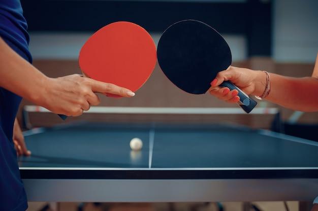 Le donne tengono racchette da ping pong, giocatori di ping-pong