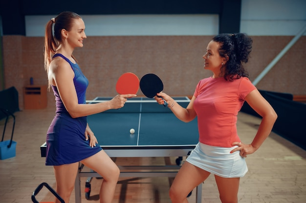 Le donne tengono racchette da ping pong