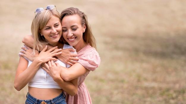 Donne che abbracciano la sua amica da dietro con lo spazio della copia