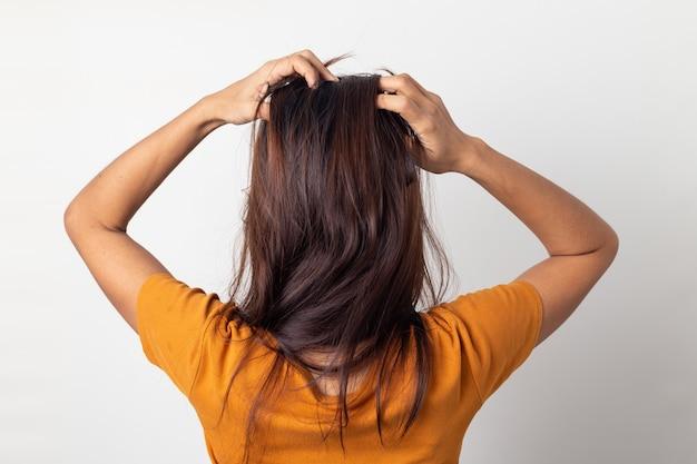 Le donne prurito del cuoio capelluto gli prurivano i capelli e le massaggiava i capelli su uno sfondo bianco