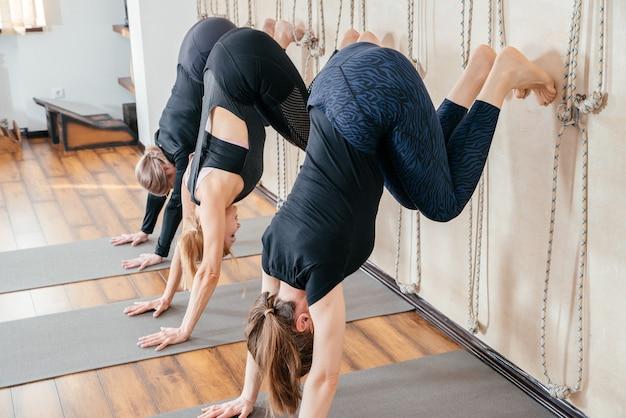 Donne che imparano a stare sulle mani vicino al muro in studio. posizione yoga capovolta