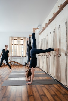 Donne che imparano a stare sulle mani vicino al muro in studio. posizione yoga capovolta