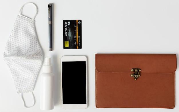 Borsa da donna in pelle con oggetti necessari, maschere di stoffa, alcool spray, gel per le mani, carta di credito, penna e telefono cellulare per l'igiene, posa piatta