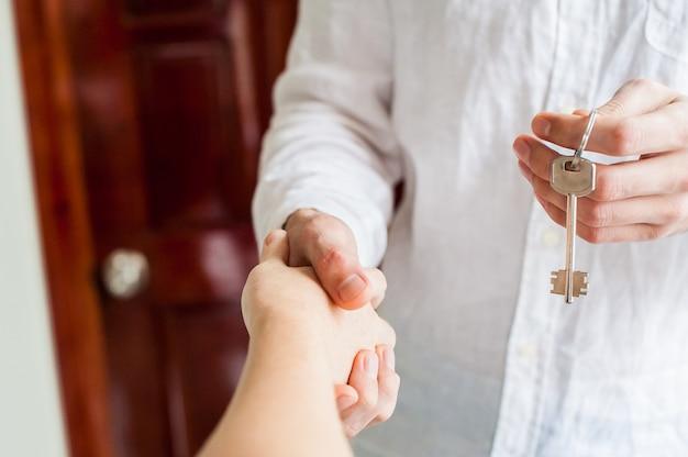 Le donne e l'uomo si stringono la mano solo per vedere una chiave viene data sullo sfondo della porta di legno. possedere il concetto immobiliare