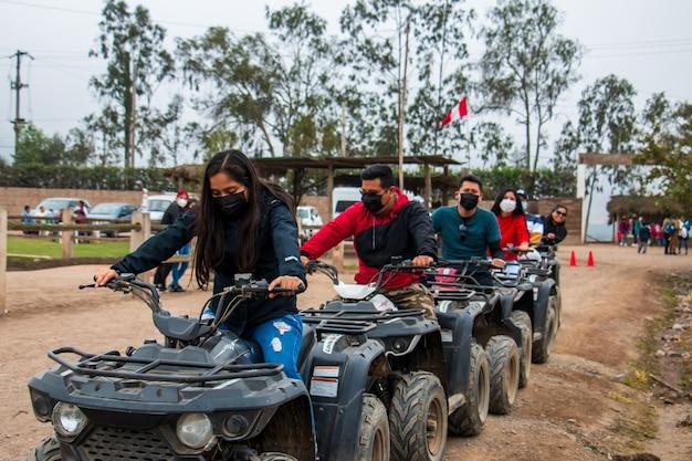 Donne e uomini su atv si stanno godendo un giro in un campo