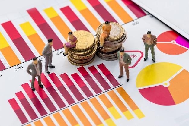 Donne e uomini sul grafico commerciale e sulle monete