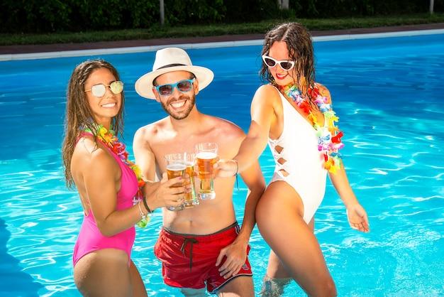 Donne e uomini festeggiano bevendo a una festa in piscina
