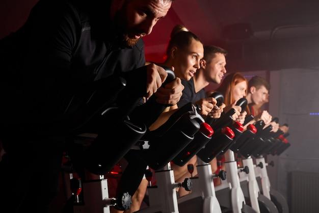 Donne e uomini sulla bici della macchina da ciclismo che lavorano nella moderna palestra in attesa, vista laterale sulle persone durante l'allenamento