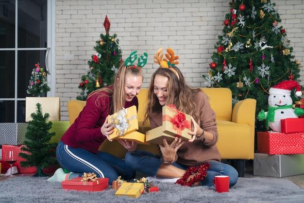 Donne che aprono la confezione regalo di natale con un amico. concetto di famiglia vacanze di natale.
