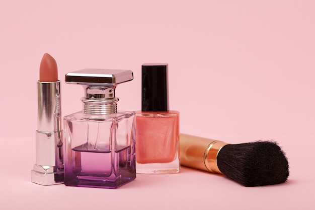 Profumo femminile, bottiglie con smalto per unghie, pennello e rossetto in uno sfondo rosa. cosmetici e profumi da donna.