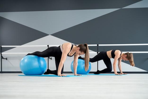 Donne che praticano la posizione della plancia utilizzando palline fitness