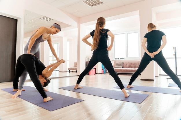 Donne che praticano pose in classe di yoga con istruttore
