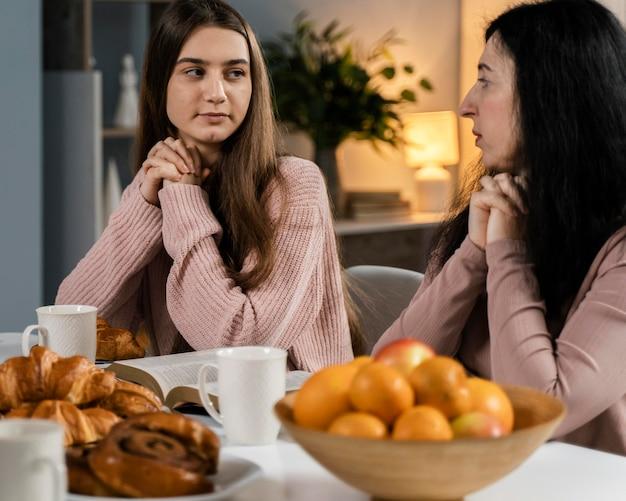 Donne che pregano prima di cena