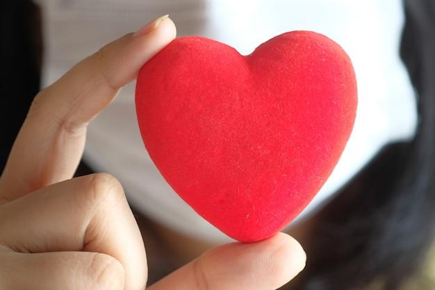 Donne in maschera protettiva che tiene cuore rosso con lo spazio della copia