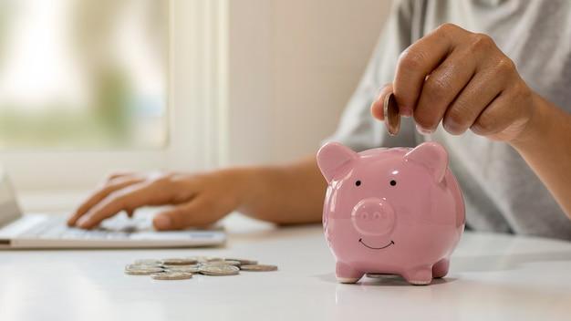Le donne mettono monete nei suinetti per risparmiare denaro