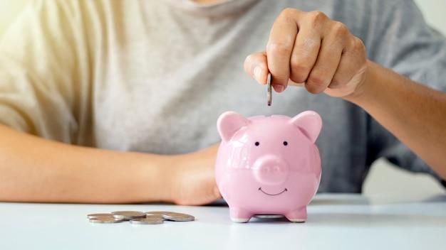 Le donne mettono monete d'argento nei maialini per risparmiare denaro
