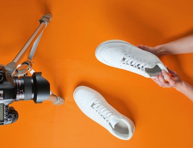 Le donne recensiscono nuove scarpe da ginnastica bianche con fotocamera su treppiede su sfondo arancione. vista dall'alto. minimalismo