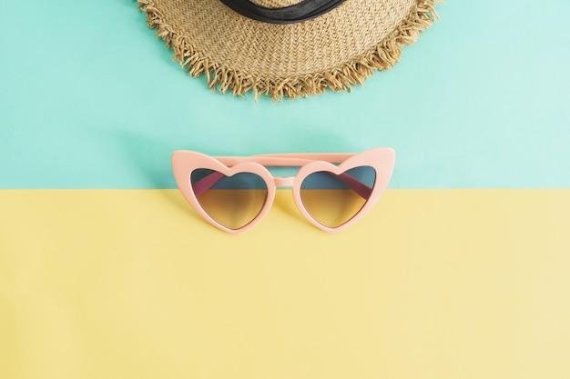 Gli articoli degli accessori delle donne sul fondo di colori pastelli, concetto di vacanze estive