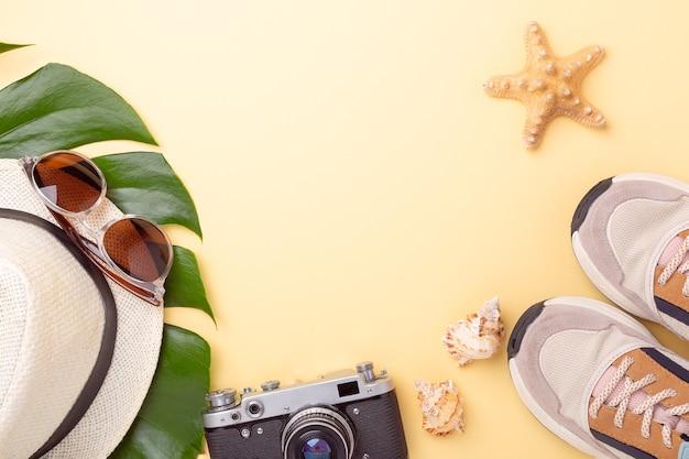 Articoli di accessori da donna su sfondo giallo pastello, concetto di vacanza estiva.