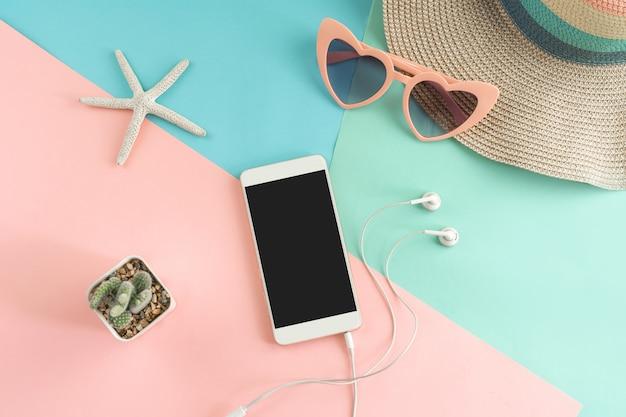 Gli articoli degli accessori delle donne con lo smart phone su fondo di colori pastelli, concetto di vacanze estive