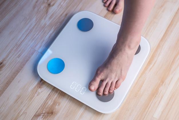 I piedi nudi delle donne stanno su bilance elettroniche sul pavimento di legno