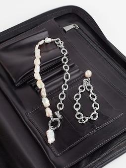 Collana di perle barocche da donna e bracciale a catena con ciondolo su borsa cosmetica femminile in pelle nera. primo piano