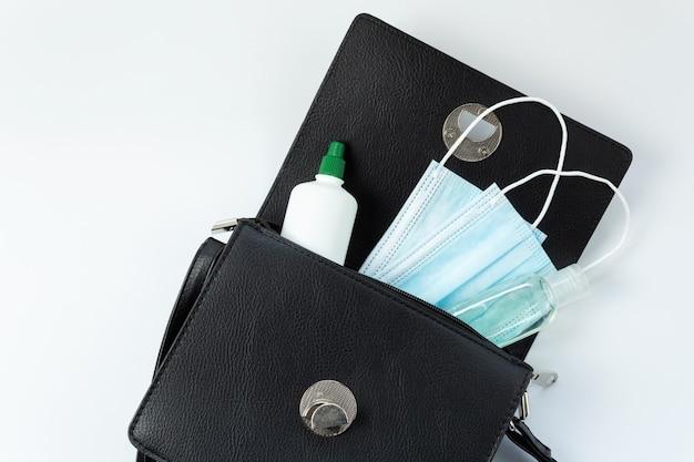 Borsa nera da donna con le cose necessarie, antisettico, mascherina medica, su uno sfondo bianco, vista dall'alto, isolata