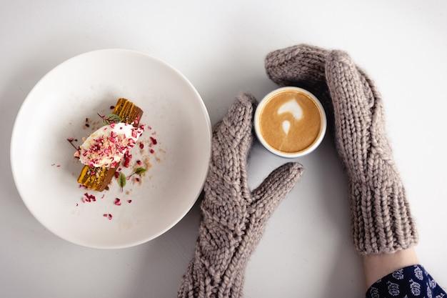 Le mani guantate marroni delle donne tengono una tazza di caffè e una torta accanto ad essa su un tavolo bianco da vicino
