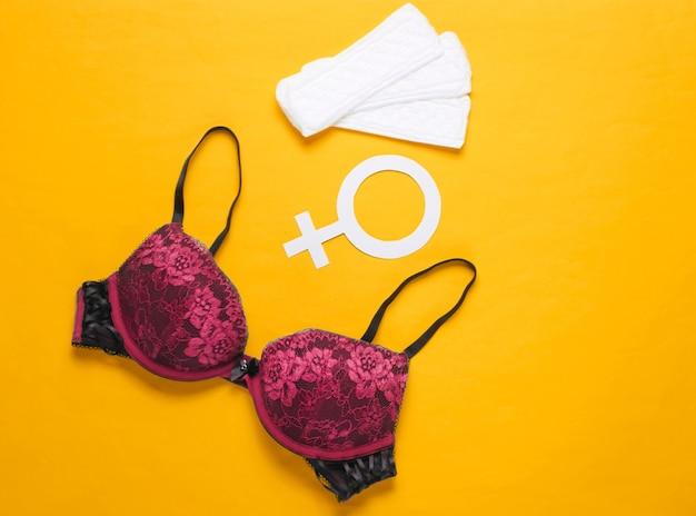 Giorni critici delle donne, mestruazioni. concetto di igiene femminile minimalista. bellissimo reggiseno sexy, salvaslip, simbolo di genere su giallo