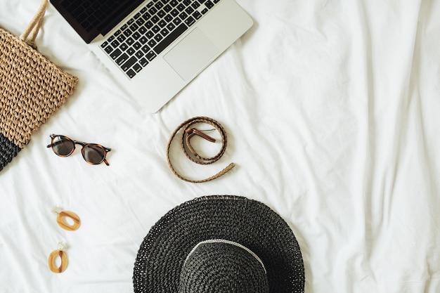 Accessori moda donna, occhiali, orecchini, cintura, cappello di paglia, borsa di paglia e laptop sdraiato sul letto con lenzuola bianche
