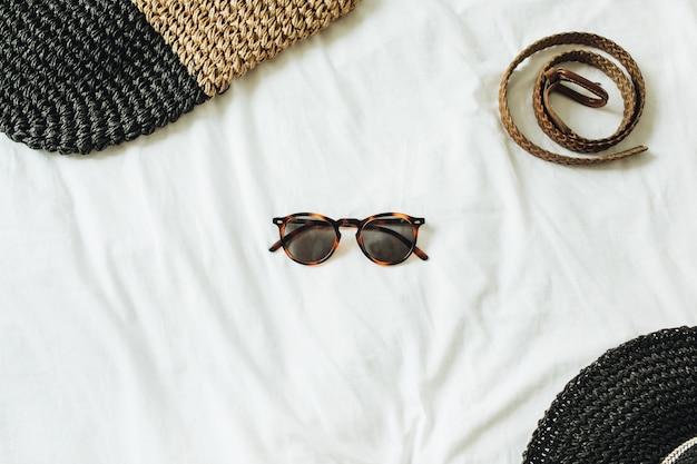 Accessori moda donna con occhiali al centro della foto e cintura, cappello di paglia, borsa di paglia sdraiata sul letto con lenzuolo bianco
