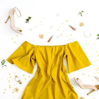 Vestiti e accessori di moda delle donne su bianco. look in stile dorato femminile piatto laico con vestito, tacchi alti, orologio, bracciale