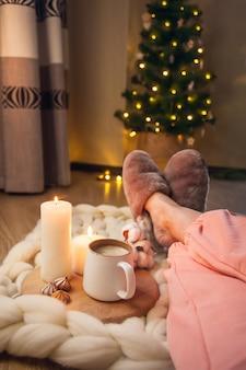 Piedi delle donne in pantofole di pelliccia domestica, tazza di cappuccino, candele su una coperta di filato spesso e albero di natale con luci. l'atmosfera di familiarità e comfort