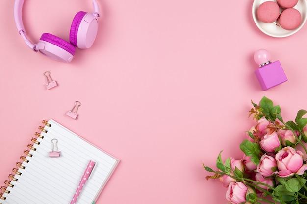 Cose di donne o ragazze, cuffie senza fili, rose, profumi, articoli di cancelleria su sfondo rosa