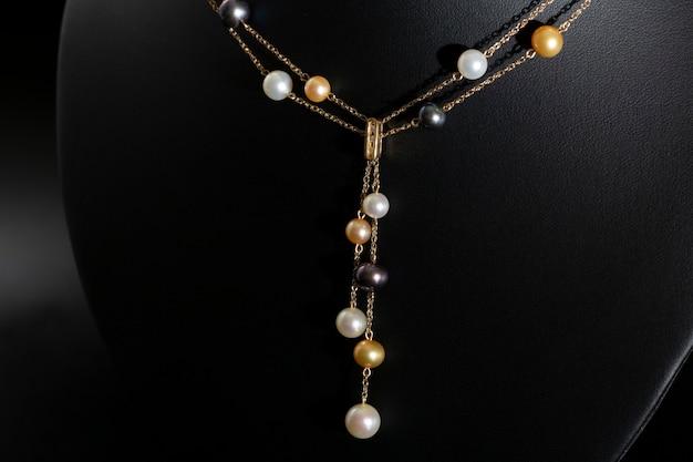 Collana in oro da donna composta da catene e perle su supporto nero. avvicinamento