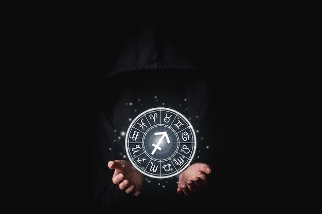 La mano delle donne nel buio tiene incandescente segni astrologici dello zodiaco in un cerchio.