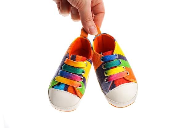 La mano delle donne tiene le scarpe sportive in denim multicolori su uno sfondo bianco. il concetto di abbigliamento per bambini.