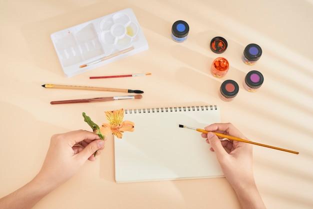 Mano femminile con disegno a pennello sul blocco note. processo di creazione della pittura ad acquerello