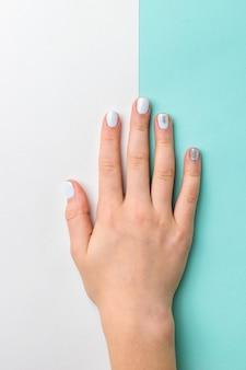 Mano delle donne con elegante trucco leggero su sfondo bianco e blu. prenditi cura delle mani.