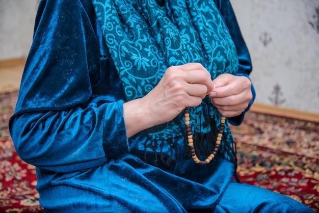 Le mani delle donne stanno sistemando le perle di preghiera musulmane